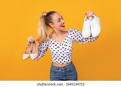 Making Decision. Portrait of smiling lady holding pair of high heels shoes and white sneakers in hands, can't choose between footwear and style, isolated over orange studio background