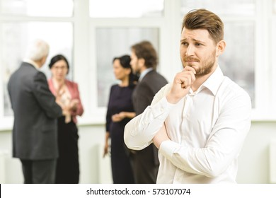 Making a decision. Young businessman thinking with his hand to his chin his colleagues business team on the background copyspace unsure solution problem thoughtful teamwork decide office concept