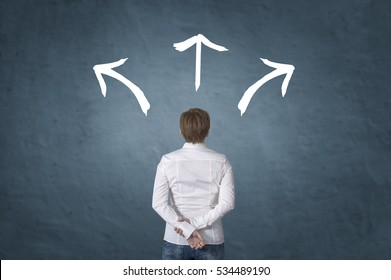 Making decisions for the future businesswoman standing in front of three direction arrow choices, left, right or move forward.
