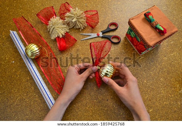 Making decoration of Christmas with spheres and red ribbon for gifts.
