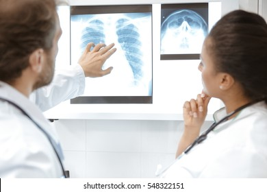 Making a diagnosis. Male doctor pointing at the spot on an x-ray he is examining with his female colleague at the hospital teamwork experience healthcare x-ray survey treatment research concept