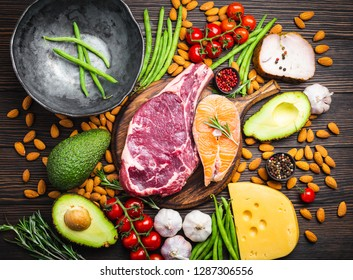 Making dinner with low carbs ingredients for healthy eating concept and weight loss, top view. Keto foods: meat, fish, avocado, cheese, vegetables, nuts. Ketogenic diet, organic clean eating