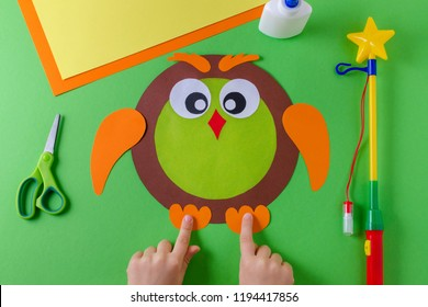 making of diy lantern for sankt martin, traditional german feast, childs hands and owl of color paper, glue, scissors, lanterns wand