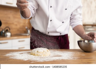 Making dough with flour powder by male hands at bakery