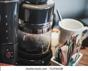 Making drip black coffee by Coffee Maker Machine, closeup with selective focus on table background