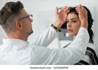 Making face measurements. Dark-haired woman standing calm while plastic surgeon making face measurements