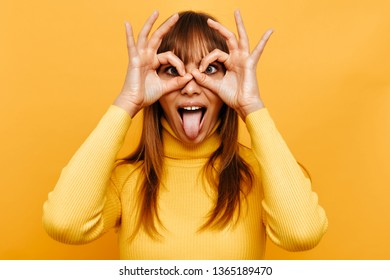 Making face Woman portrait. Fun. Cheerful young woman is grimacing and showing her tongue at camera, on a yellow background