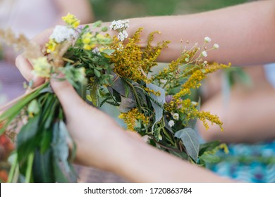 Making a Festive flower wreath,  circlet of flowers, festival coronet of flowers on a bright sunny afternoon. Preparing for Midsummer night fest, or bachelorette party idea. How to Make a Flower Crown