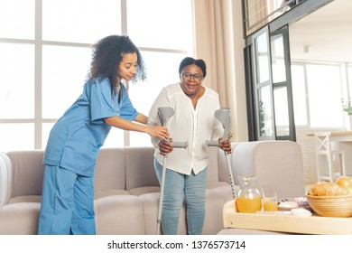 Making first steps. Aged woman feeling satisfied after making first steps after surgery on legs with the help of nurse
