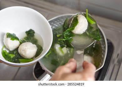 Making fish ball soup with green vegetable