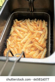 Making French Fries. French fries cooking in oil in a deep fryer