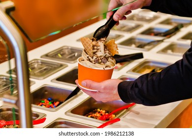 Making frozen yogurt with chocolate chips and sprinkles at the buffet