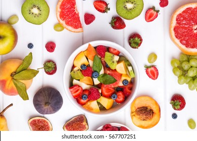 Making fruit salad. Delicious fruits and berries an the table, top view.