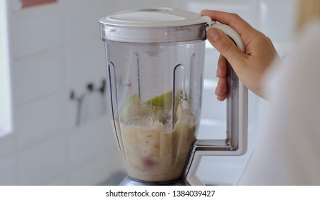 Making fruit smoothies, women's hands with a blender. Healthy diet at home in the kitchen