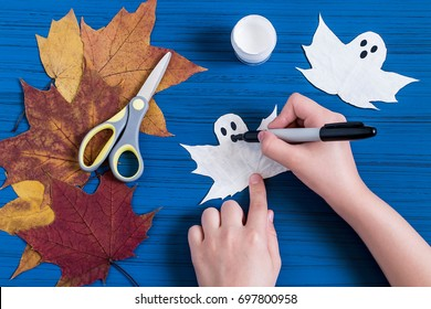 / Making ghosts from maple leaves to Halloween. Halloween decor of room. Children's art project. DIY concept. Step-by-step photo instructions. Step 4. Child draws eyes and mouth of ghost