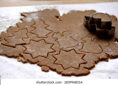 Making gingerbread cookies for Christmas. Pine tree, star and squirrel shaped cookie cutters.