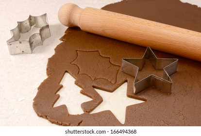 Making gingerbread cookies with cutter and wooden rolling pin