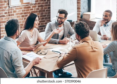 Photo of Making great decisions. Young beautiful woman gesturing and discussing something with smile while her coworkers listening to her sitting at the office table