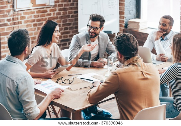 Making great decisions. Young beautiful woman gesturing and discussing something with smile while her coworkers listening to her sitting at the office table