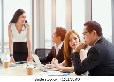 Making great decisions. Young woman gesturing and discussing something with smile while her coworkers listening to her sitting at the office table