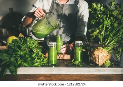 Making green detox take-away smoothie. Woman in linen apron pouring green smoothie drink from blender to bottle surrounded with vegetables and greens. Healthy, clean eating, weight loss food concept