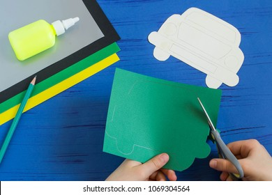 Making greeting card for Father's Day in shape of car. Children's art project. DIY concept. Step-by-step photo instruction. Step 3. Child carves card in shape of car