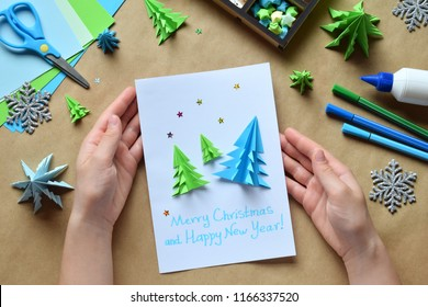 Making greeting card with origami 3D Xmas tree from paper. Merry Christmas and Happy New Year decoration. Children's DIY concept. Handmade crafts on holiday with your own hands.