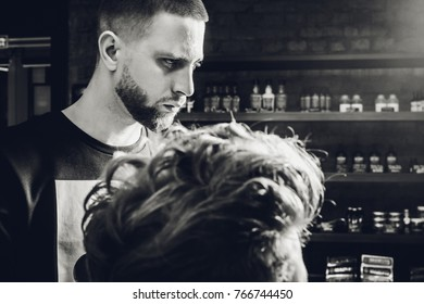 Making haircut look perfect. Young bearded man getting haircut by hairdresser while sitting in chair at barbershop