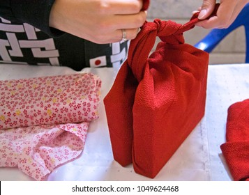 Making handmade bag of folded red cloth. Furoshiki - Japan art of folding cloth. Concept of fashion & reusable eco-bag contrary to plastic bags. Selective focus