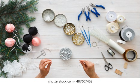 Making handmade christmas balls. Woman's leisure, tools for creating holiday decorations and garland. Top view of white wooden table with female hands holding various trinkets, decor accessoires