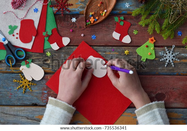 Making of handmade christmas toys from felt with your own hands. Children's DIY concept. Making xmas tree decoration or greeting card. Step 1. Circle the stencil