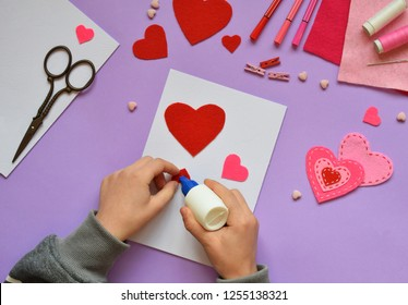 Making of handmade Valentine greeting card from felt. Children's DIY, hobby concept, gift with your own hands. Valentine's Day decoration. Step 3. Stick the heart template on card