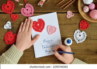 Making of handmade Valentine greeting card with crochet openwork hearts. Making of handmade decoration. Valentines Day crafts. Childrens DIY, hobby concept, gift with your own hands.