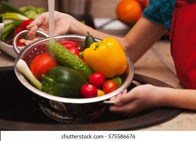 Making a healthy salad, washing ingredients - various vegetables under the water jet in child hands, shallow depth