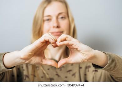 Making a heart hand gesture