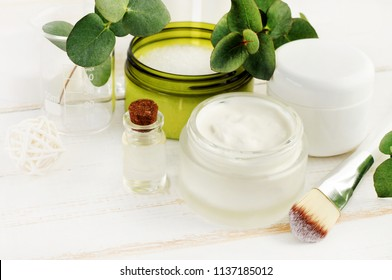 Making herbal beauty care remedy of oil, green holistic plants, fresh cream, sea salt. Jars and bottles with cosmetic products set on white wooden table.