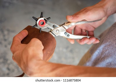 Making holes with puncher in leather workshop. Male hands with eyelet puncher working with piece of material