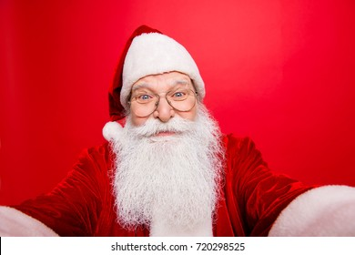 Making holly jolly x mas noel festive memories. Close up of funny Saint Nicholas photographer in red traditional fur coat and head wear is taking shot on camera, isolated on red background