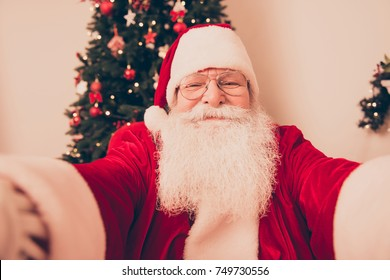 Making holly jolly x mas noel festive memories. Close up of funny Saint Nicholas photographer in red traditional fur coat and head wear, taking shot on camera, indoors, pine fir tree behind