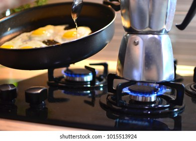 Making home breakfast with scrambled eggs and coffee on gas stove.