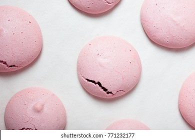 Making homemade French Macarons with raspberry coffee flavor: imperfect, light pink macaron shells with little cracks on white parchment paper after baking