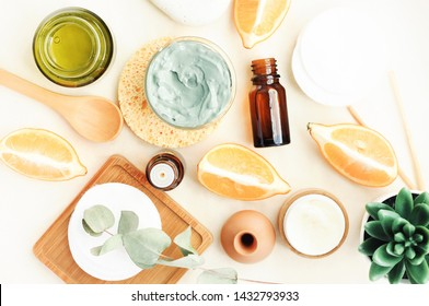 Making homemade skin care cosmetic mask with essential oil of lemon of cleansing mud clay. Jars & bottles, beauty treatment ingredients top view on table light background