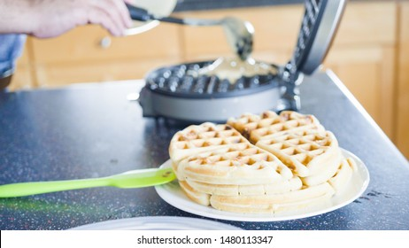 Making homemade waffles in an electric waffle maker.