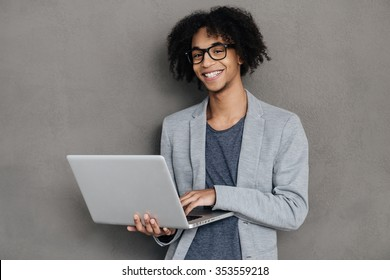 Making ideas happen. Cheerful young African man holding laptop and smiling while standing against grey background