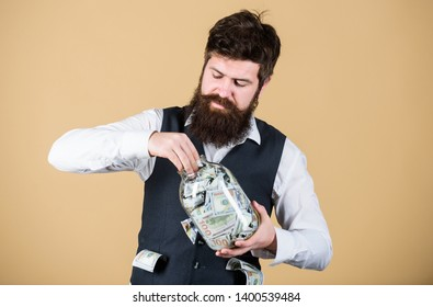 Making an investment. Businessman taking cash money out of glass jar for investing activities. Bearded man investing money into startup business. Investing for future benefit. Investing capitalist.