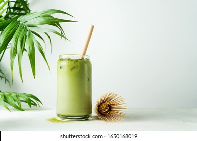 Making Japanese iced matcha latte, green tea with milk, soy milk, traditional matcha tools, with bamboo straw in glass on white background.