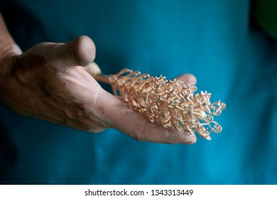 making jewelry, hands holding cast golden parts for jewelry