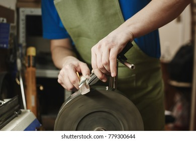 Making of a knife. Master sharpens a blade on the machine closeup in the Studio