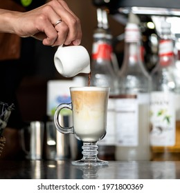 Making latte coffee. Barista pours freshly brewed coffee into whipped milk froth in front of bottles on blurred background. Glass of coffee drink with froth. Close up shot.