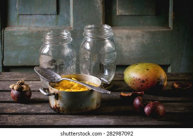 Making mango chutney or jam in vintage aluminum pan over old table with empty glass jar, mango and mangosteen. Dark rustic atmosphere